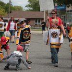 Gore Bay youth wearing hockey jerseys parade down the main street.