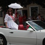 Lady in white dress rides in the backseat of a classic car.